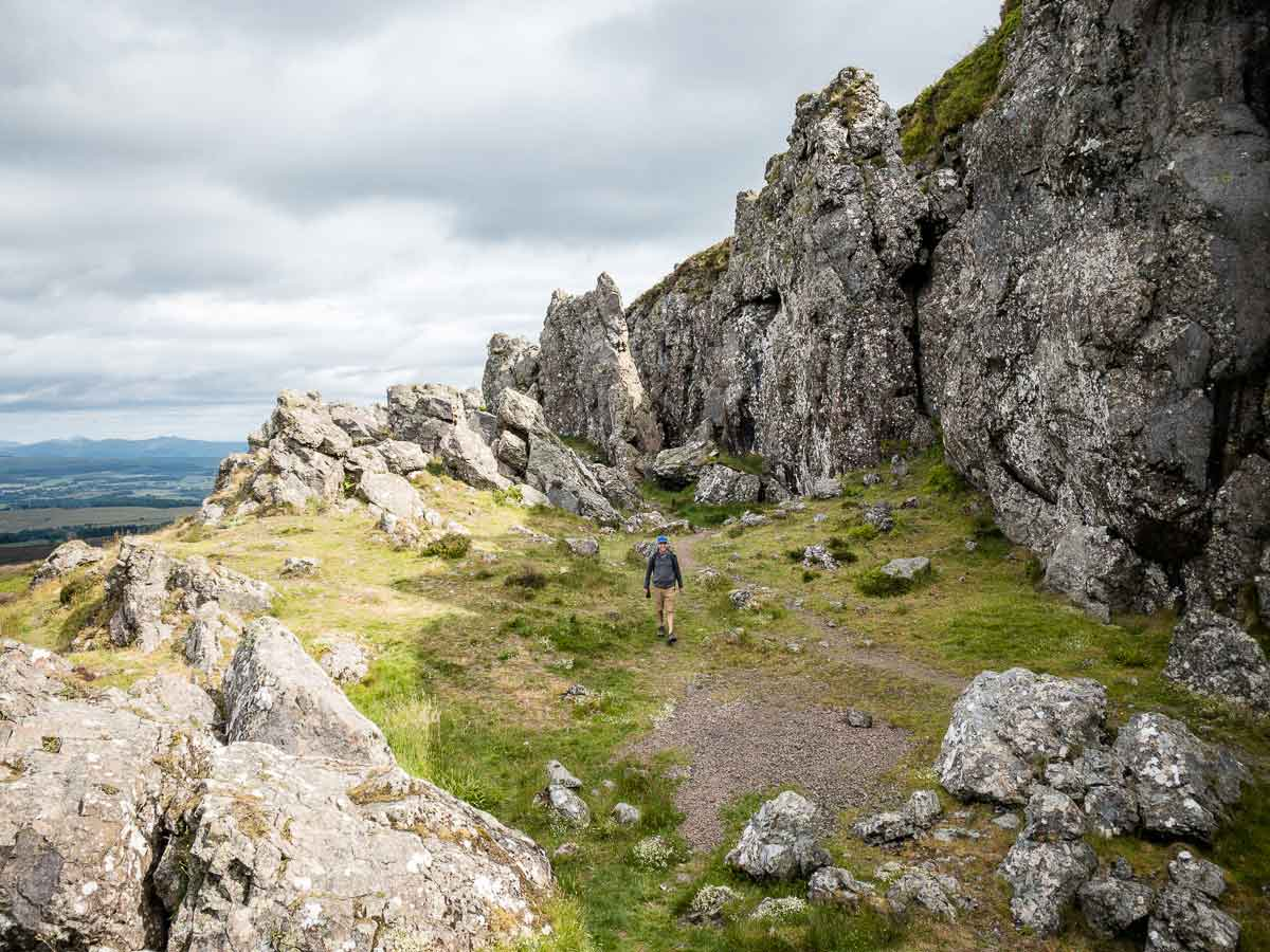 image of man walking along the huge rocks of the Whangie in Scotland