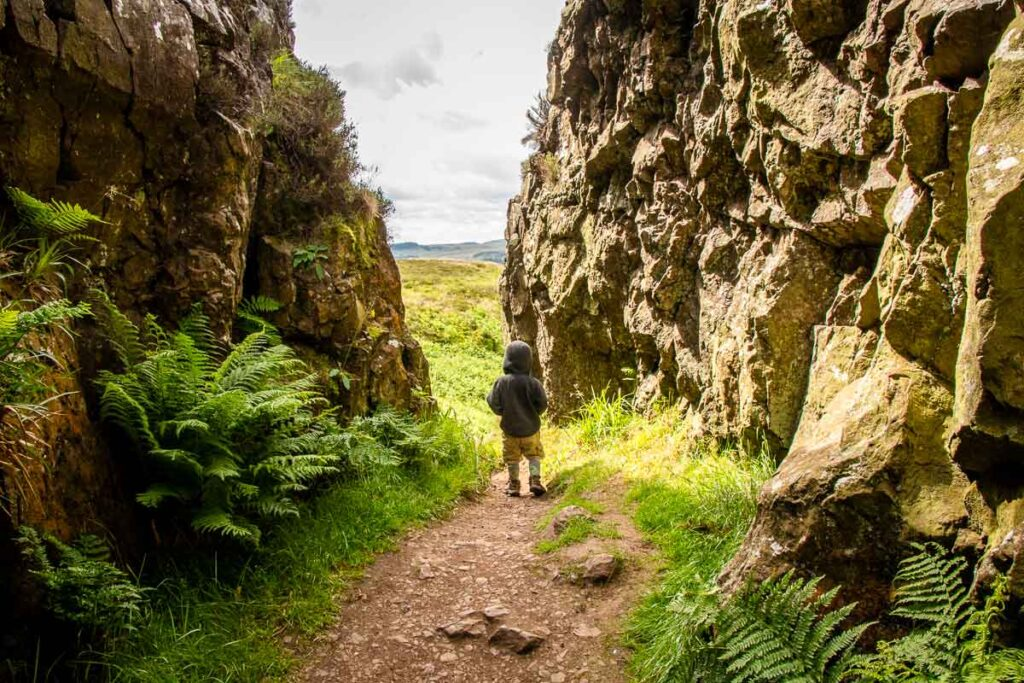 image of boy at the exit of a canyon along the Whangie hike in Scotland near Loch Lomond National Park