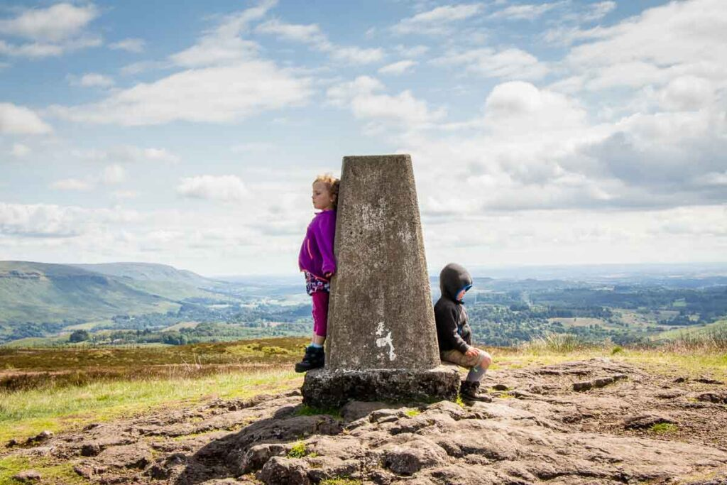 image of two kids sitting beside a monument at the top of the hill along the Whangie hill walk in Scotland near Loch Lomond National Park