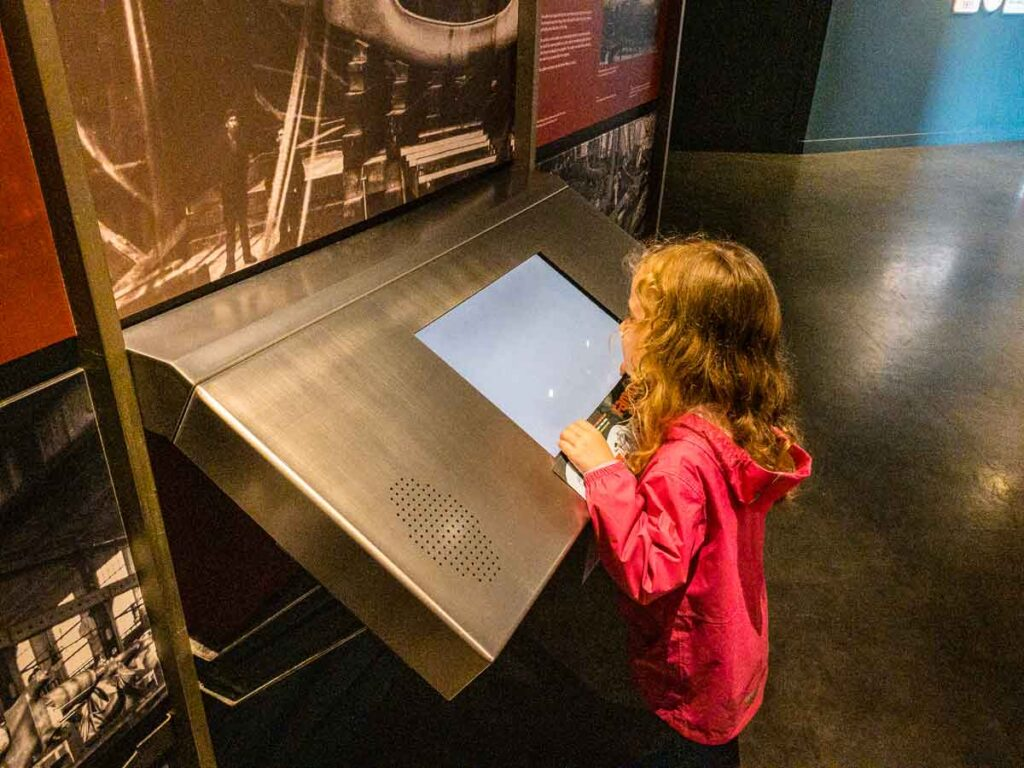 Image of girl in pink rain jacket at an exhibit in the Titanic Museum