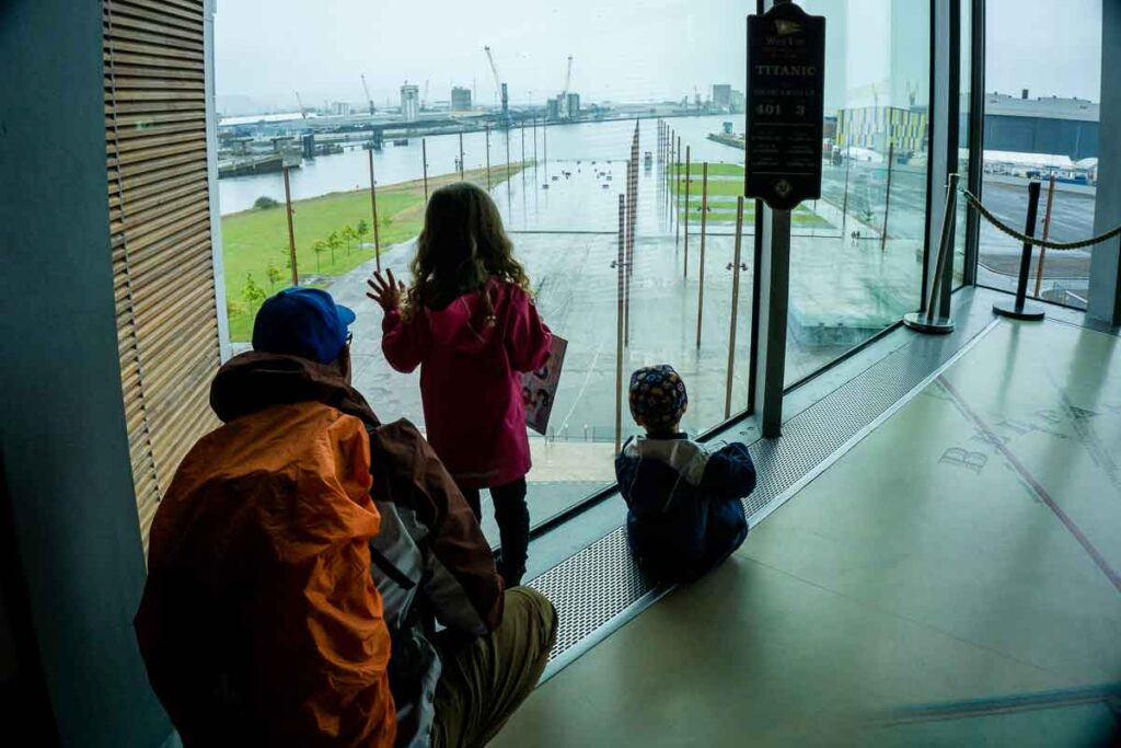 image of father and two kids at Titanic Belfast looking out the window where the Titanic once stood