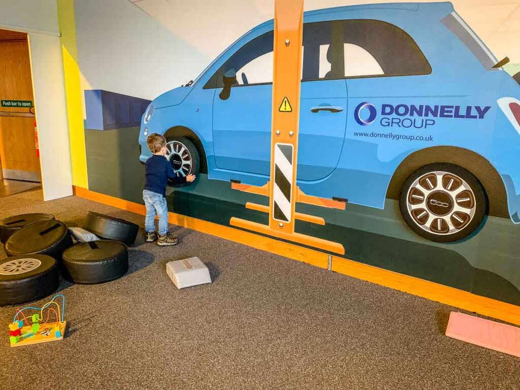 image of boy putting a play tire on a car at W5 in Belfast with Kids