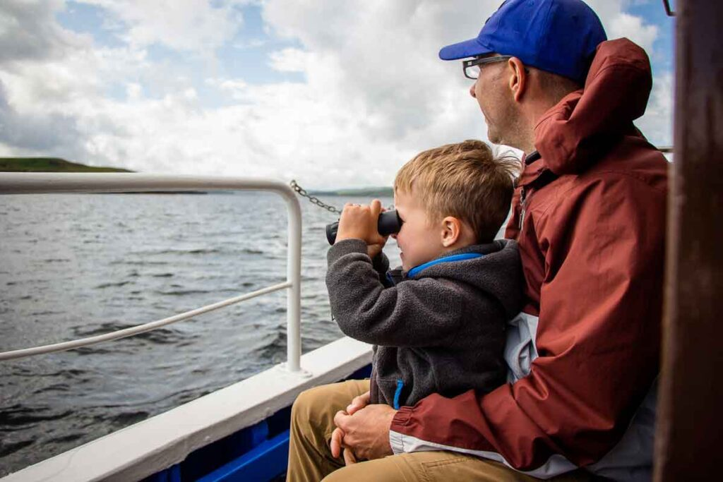 image of boy on father's lap with binoculars on Isle of Skye boat cruise