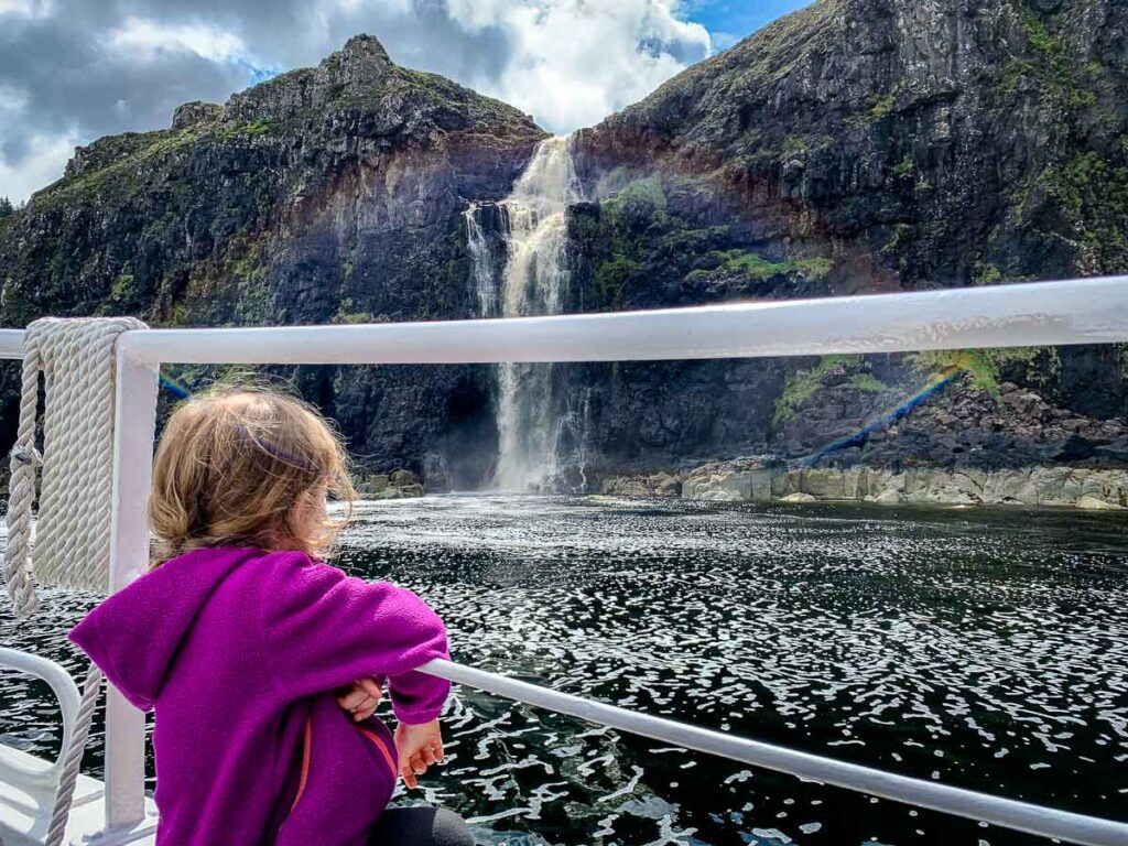 image of girl looking at waterfall from a boat on a boat cruise on Isle of Skye