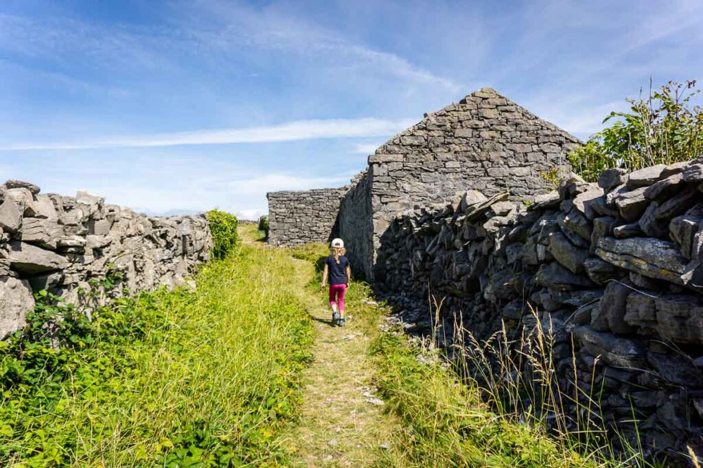 image of girl walkign along trail between stone fence on Inis More Island in Ireland