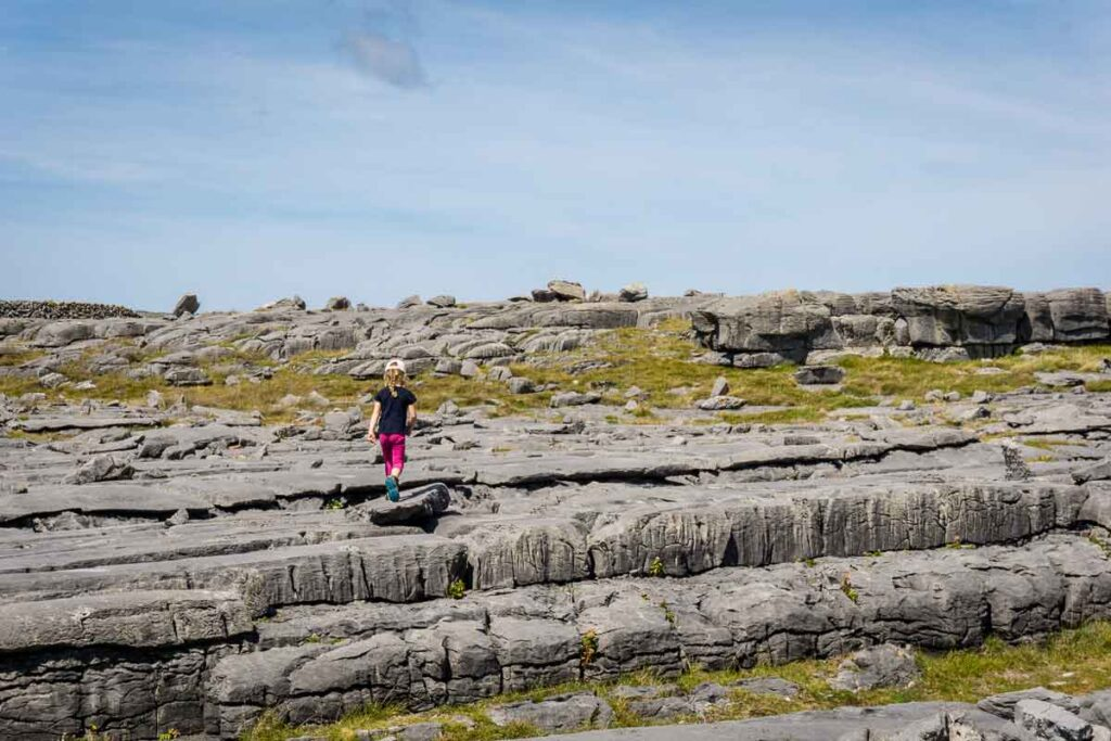 Image of girl walking across rocks on trail to the wormhole on Inis Mor Aran Island Ireland