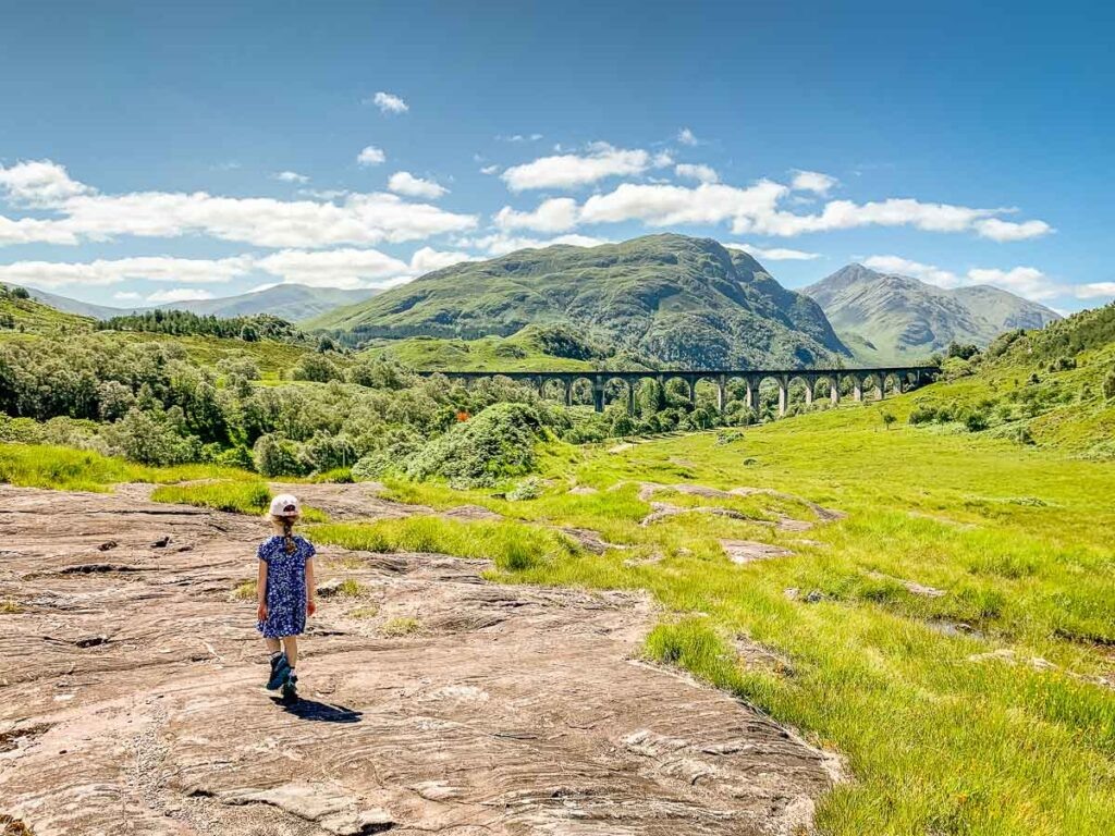 image of girl walking on a large flat rock with Glenfinnan Viaduct in the distance
