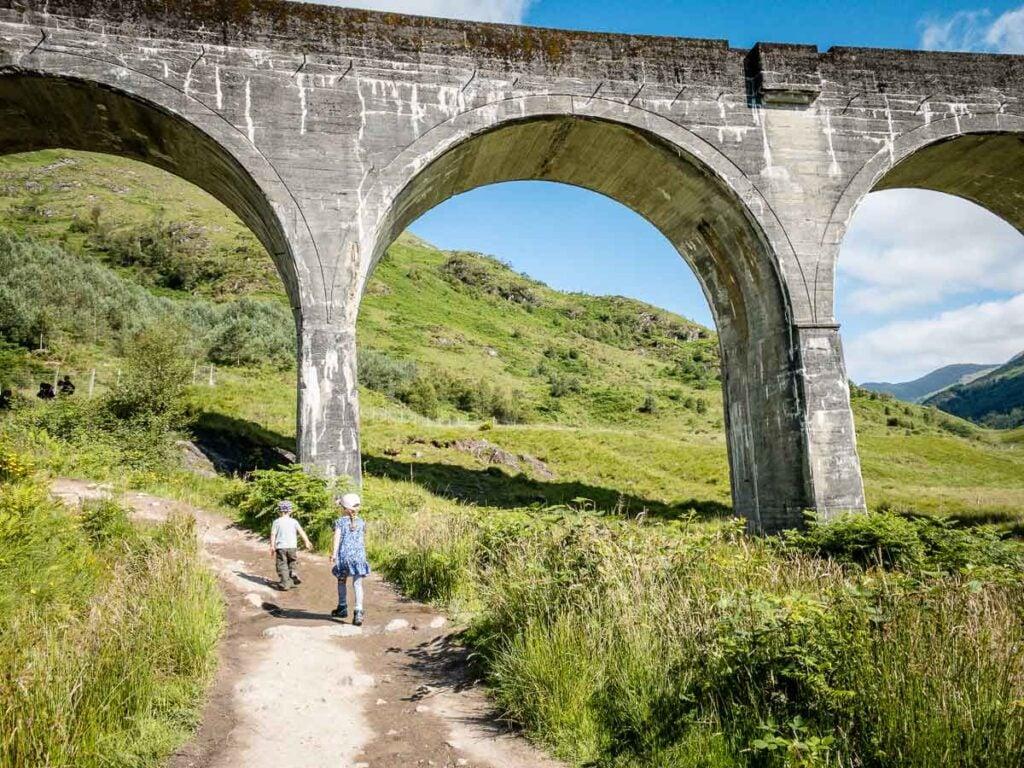 image of kids walking under Glenfinnan Viaduct Scotland