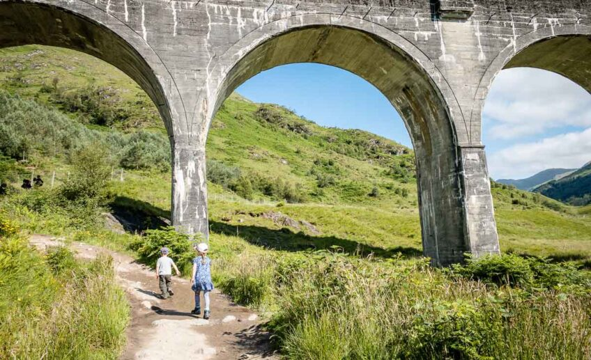 image of kids walking under Glenfinnan Viaduct Scotland