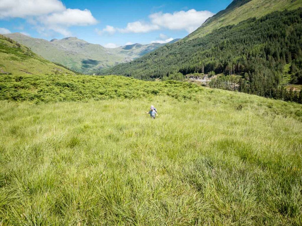 image of kids walking in long grass with mountains all around near Glenfinnan Viaduct Scotland