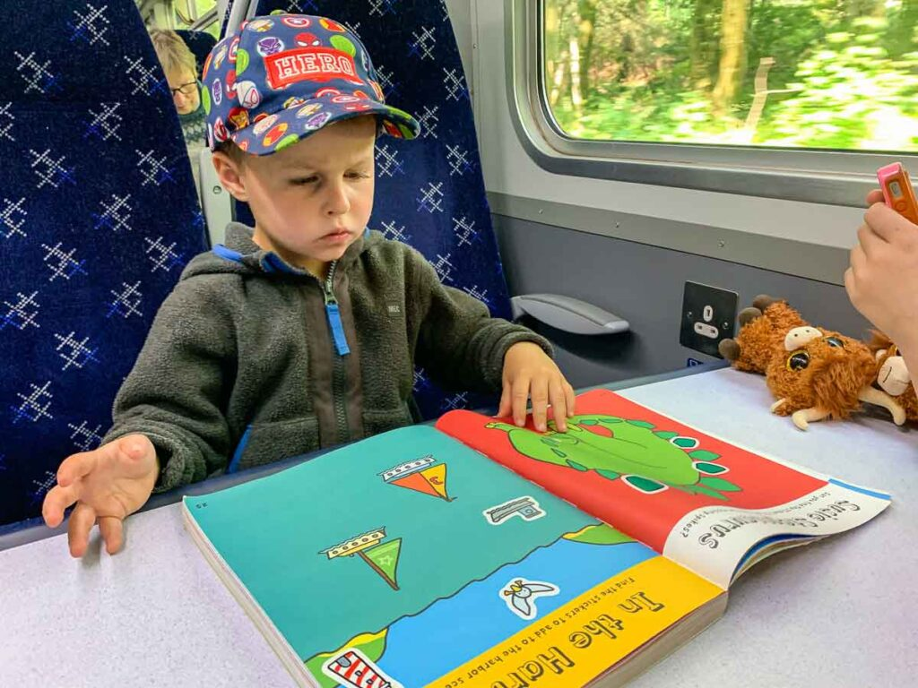 image of boy working on activity book on train in Scotland
