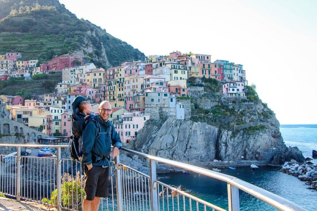image of man hiking with a baby in Cinque Terre Italy