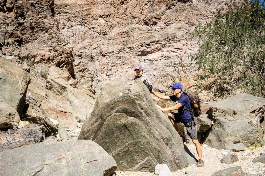 boy climbing on large rock in painted canyon - palm springs hikes