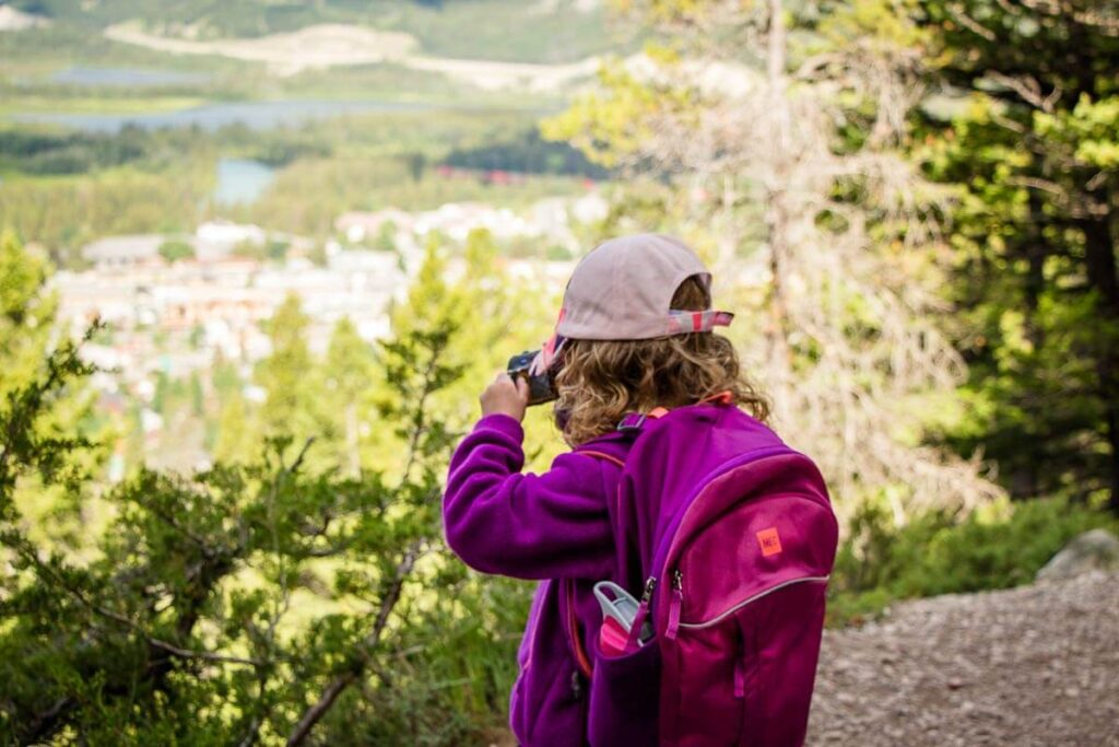 image of girl taking picture on hiking trail