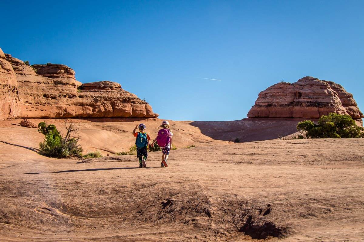 image of two kids hiking on trail to delicate arch in utah