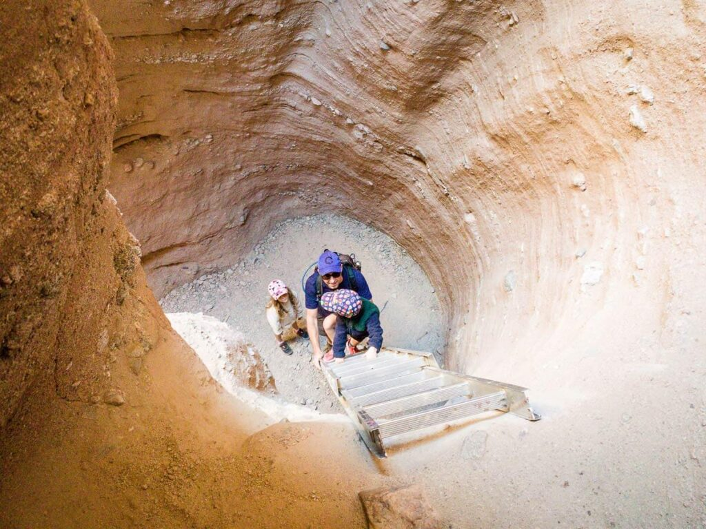 image of boy climbing ladder along ladder canyon trail - palm springs hiking