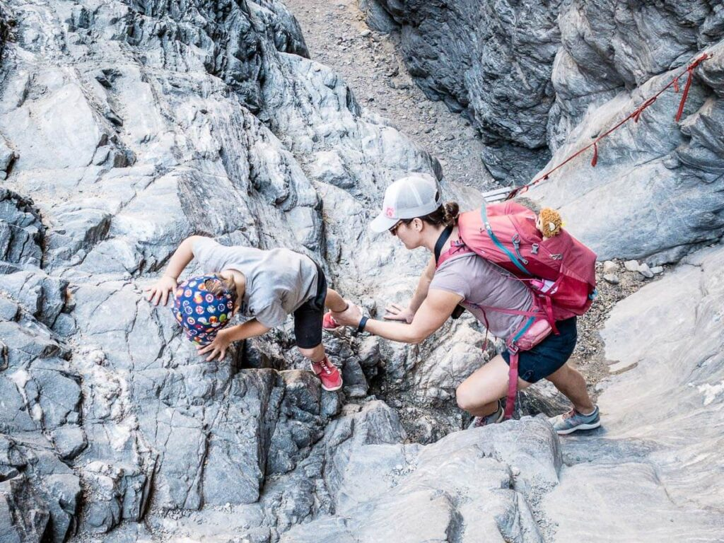 mother helping boy down to ladder in painted canyon in mecca wilderness