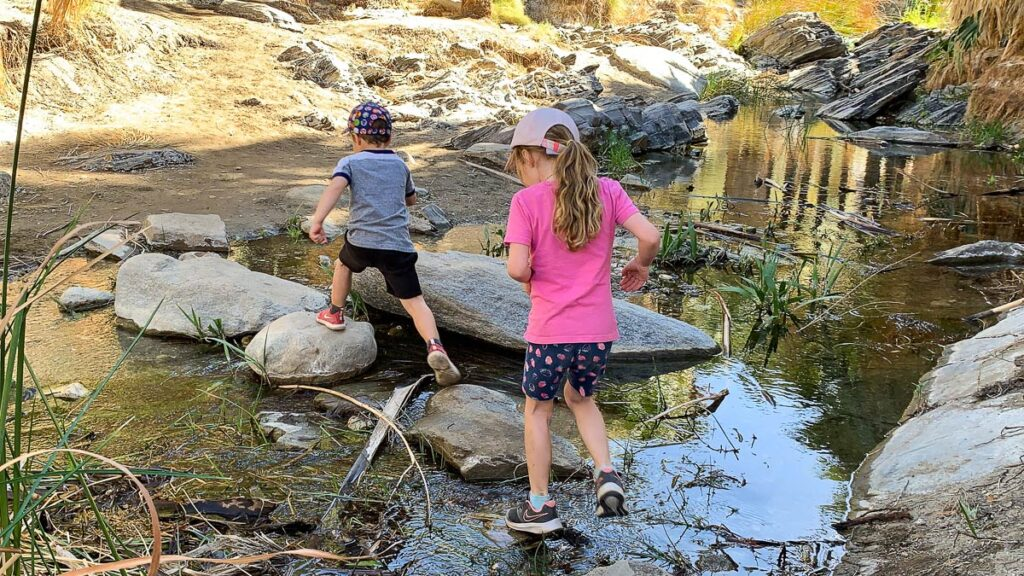 image of kids crossing steam along Palm Canyon Trail Palm Springs