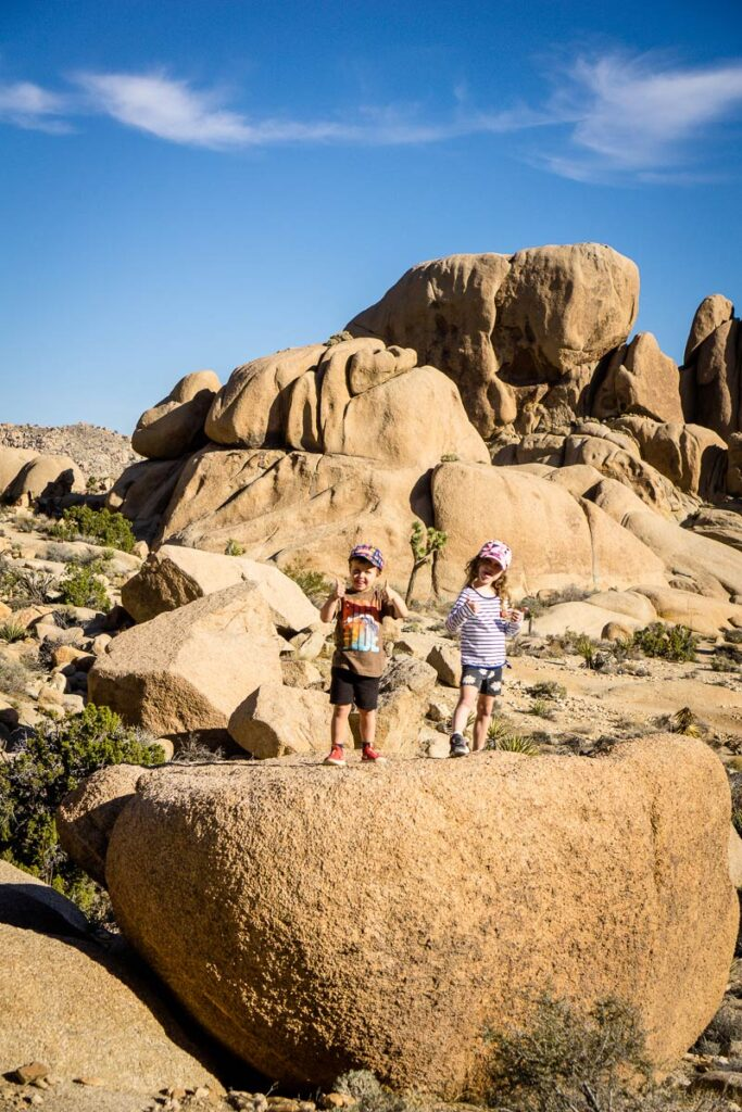 image of two kids along Split Rock, one of the best hikes in Joshua Tree with kids