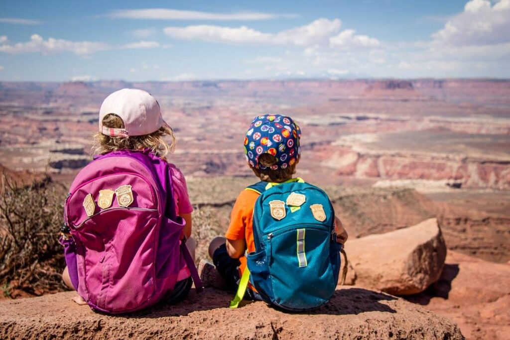 image of two kids sitting beside each other along hiking trail in Canyonlands national park utah