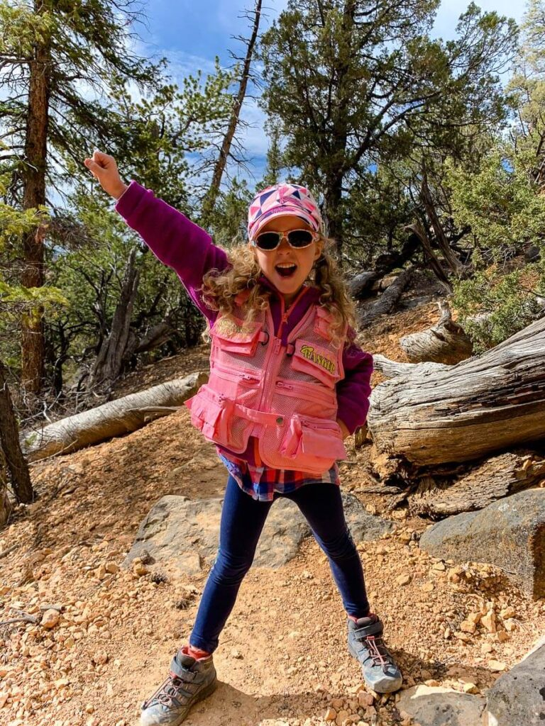 image of girl in sunglasses hat and ranger vest hiking in utah