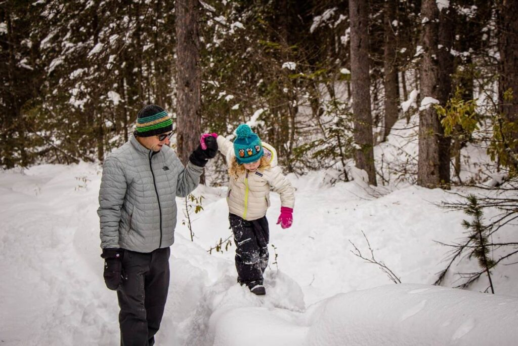 image of man and daughter hiking in snow