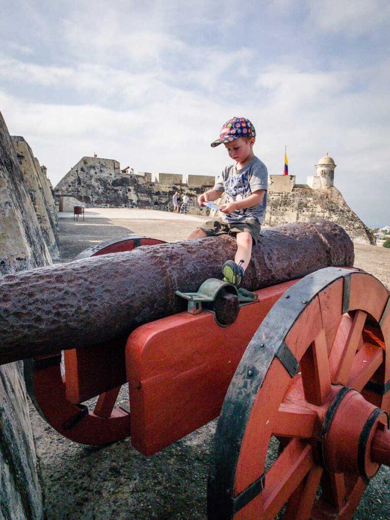 A boy sits atop a cannon at the Castillo de San Felipe de Barajas in Cartagena