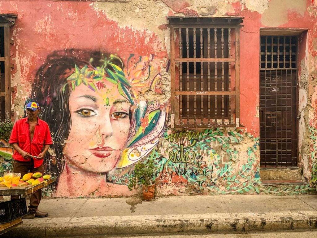 A man sells mangos next to street art in Getsemani, Cartagena, Colombia