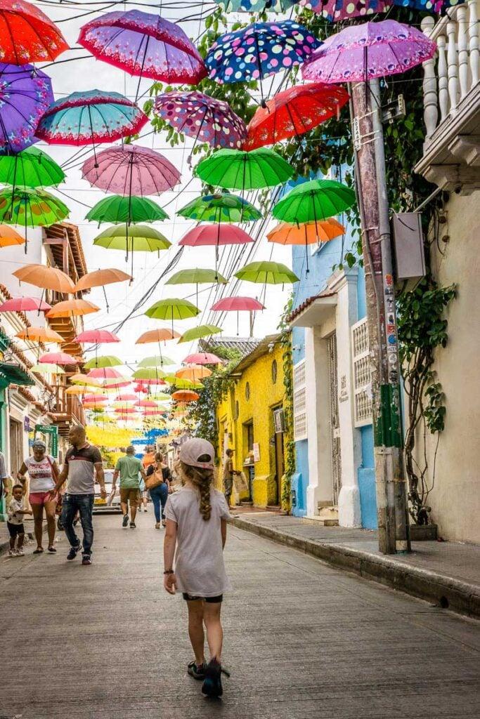 A girl enjoys an umbrella covered street in Getsemani, Cartagena