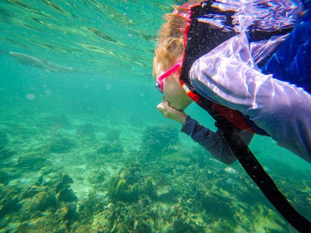 A girl learns to snorkel in the cystal clear waters near Isla Mucura, Colombia