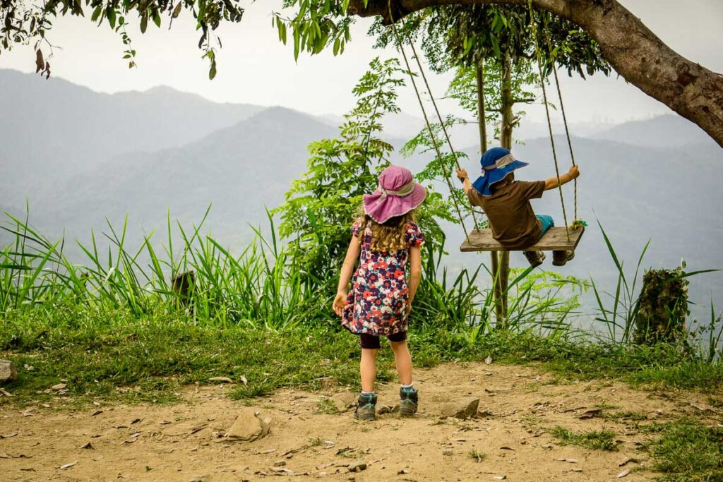 Kids play on a swing while hiking to a cacao farm near Minca, Colombia