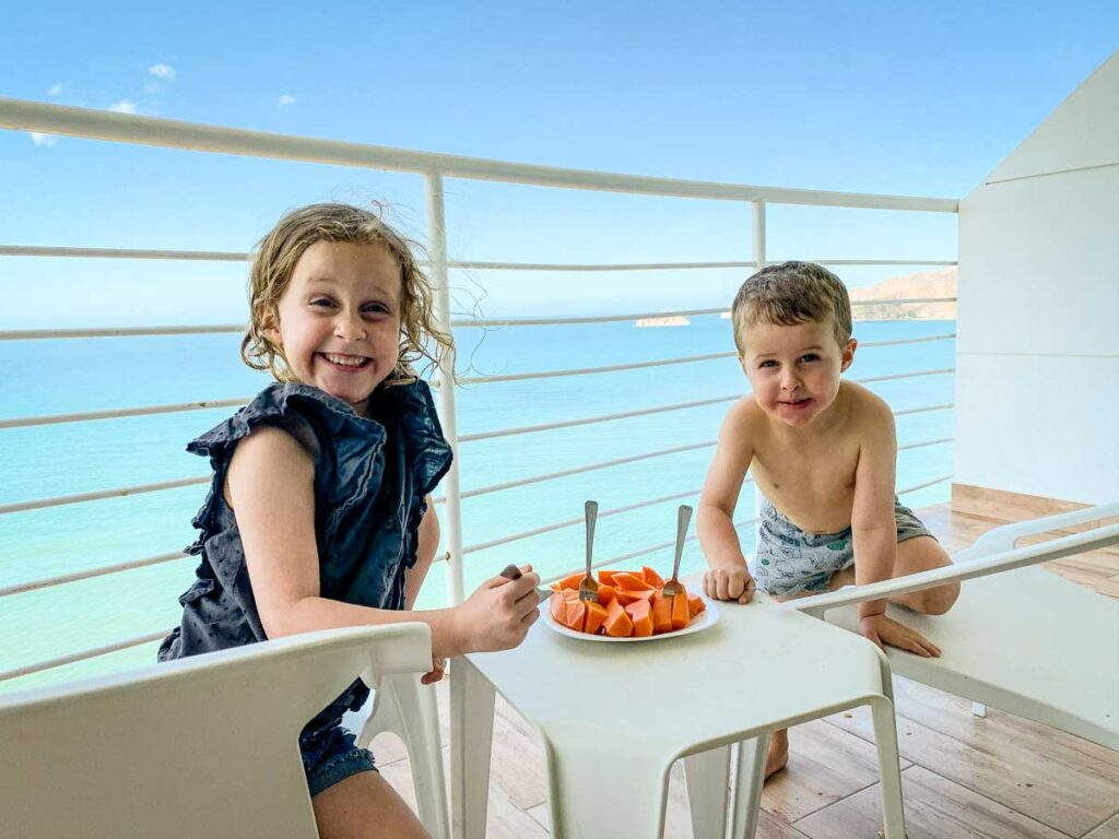 Two kids enjoying fresh papaya at an Airbnb overlooking the Caribbean in Colombia
