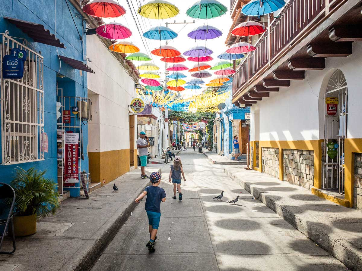 Kids walking underneath a canopy of brightly colored umbrellas in Getsemani, Cartagena
