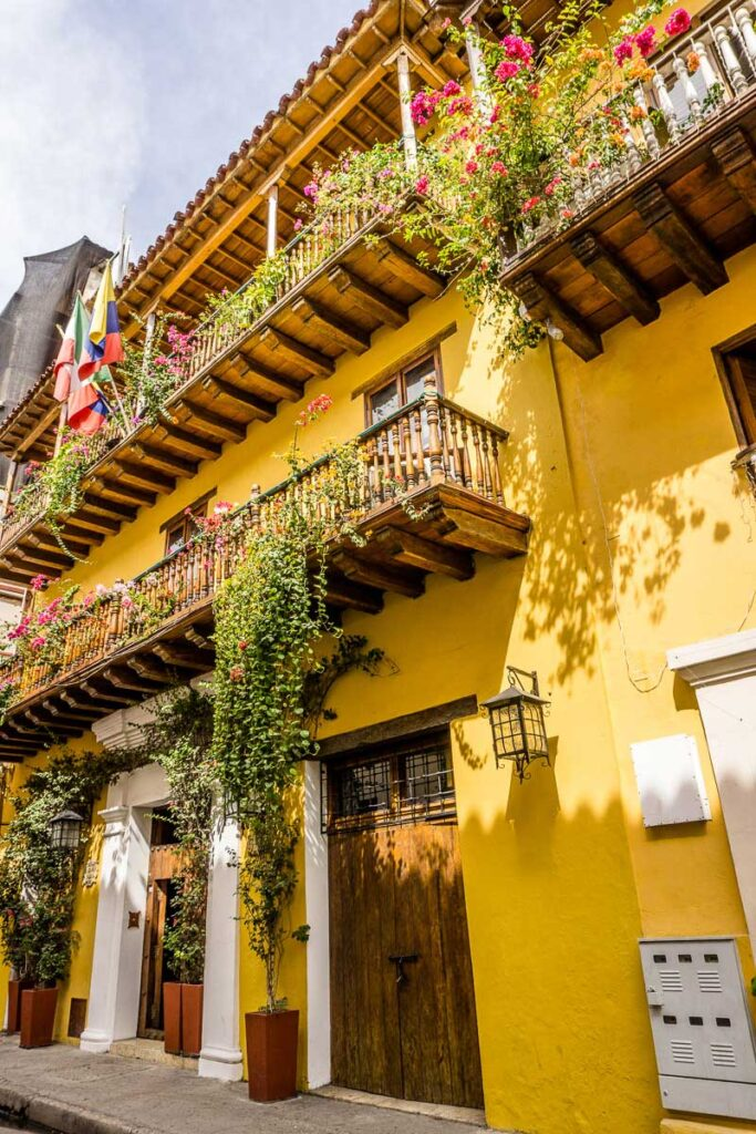 Bougainvillea flowers climbing walls and Colombian flags decorate colorful houses in Cartagena Old Town