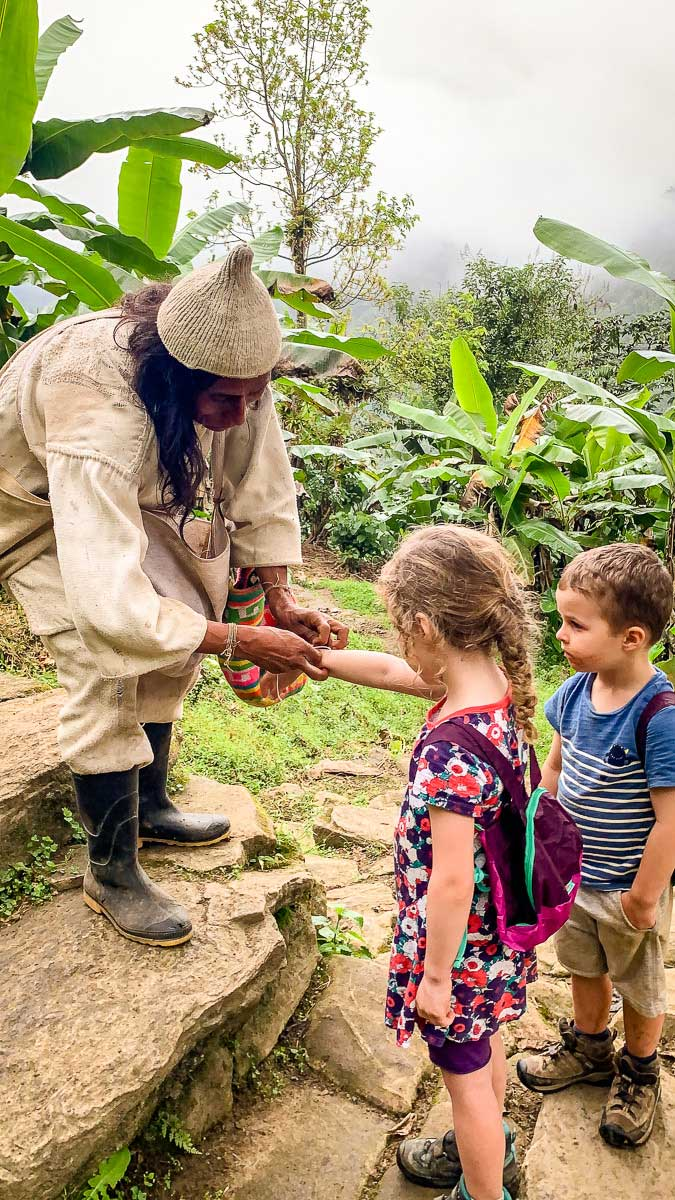 A spiritual leader gives bracelets to two kids at Ciudad Perdida