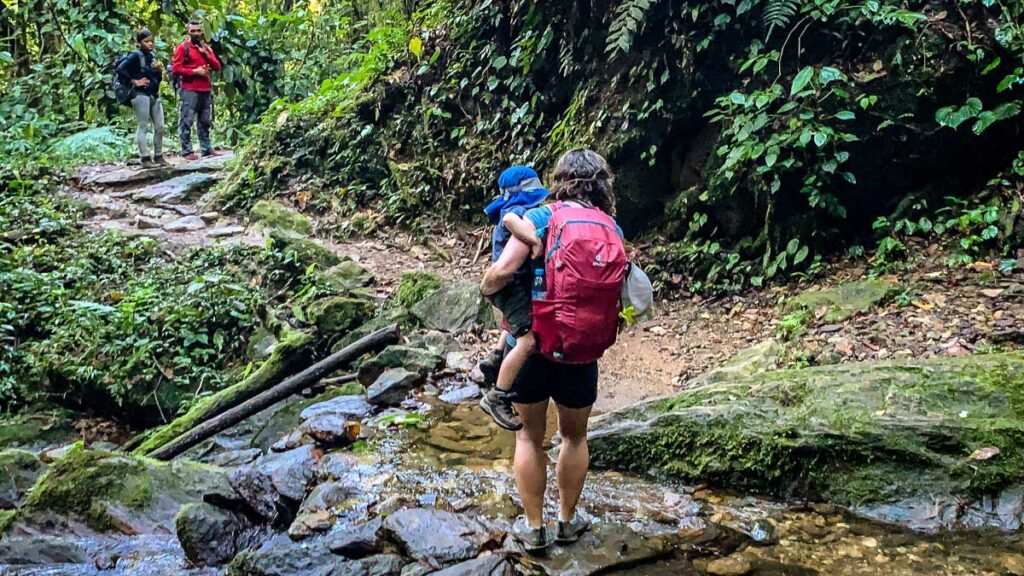 A mom helps her son cross a small stream on the way to the Lost City, Colombia