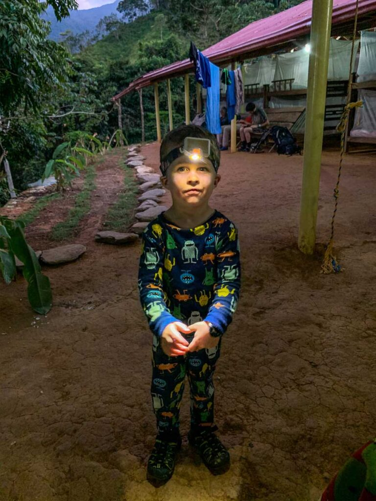 A young hiker in his pajamas and a headlamp getting ready for bed at camp on the Lost City trek
