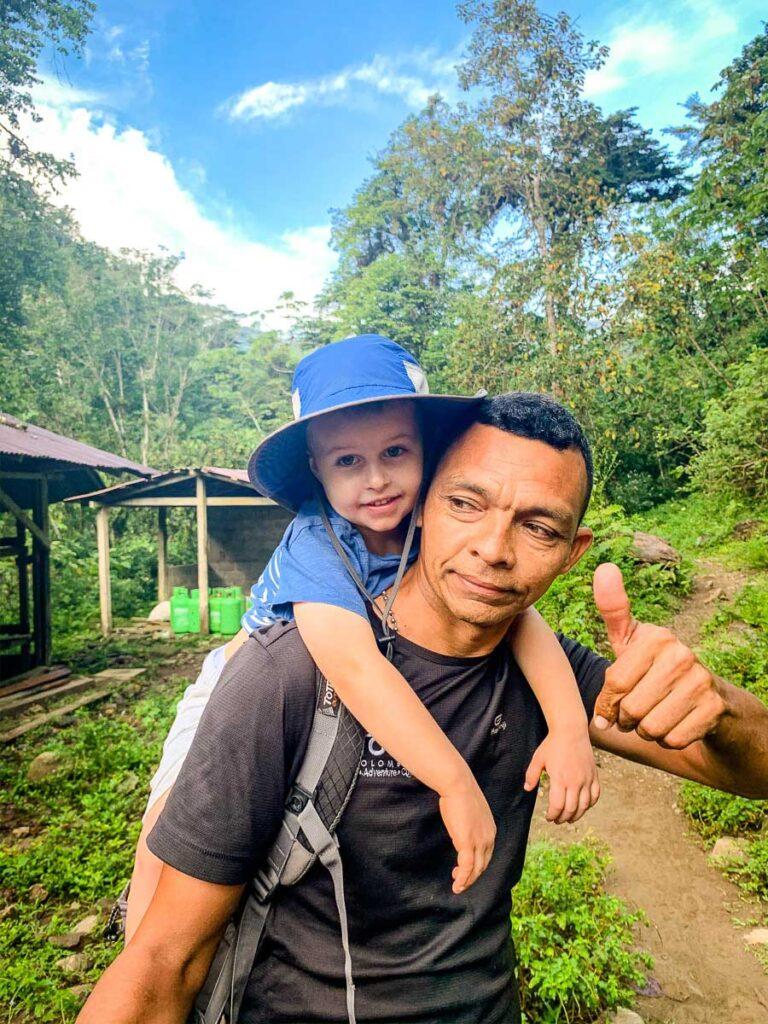 A boy gets a piggy back ride from his guide while hiking to the Lost City Colombia