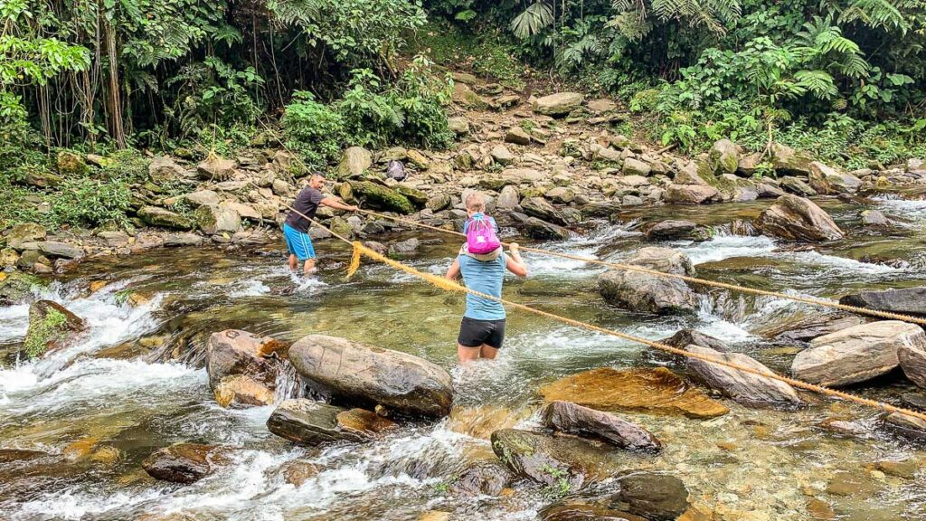 A mom and her son cross a river on the final leg of the Ciudad Perdida hike