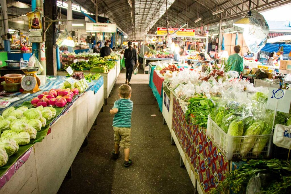 A child explores a food market in Chiang Mai, Thailand
