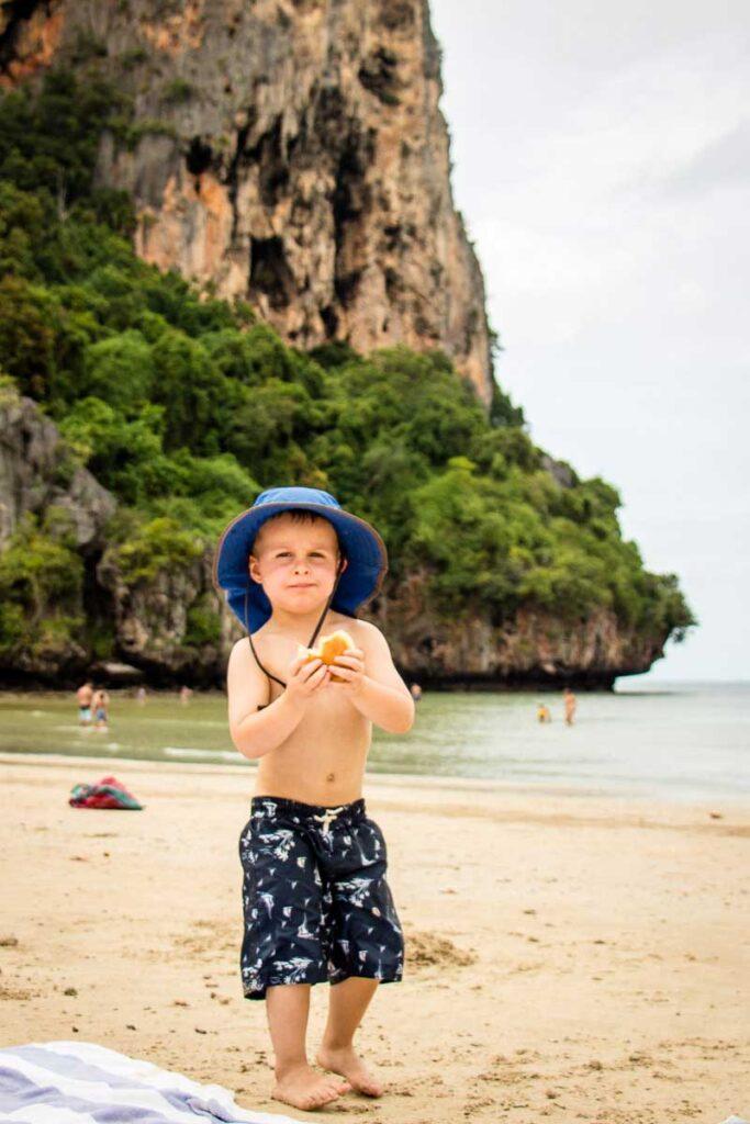A child enjoying a sandwich at Railay Beach, Thailand