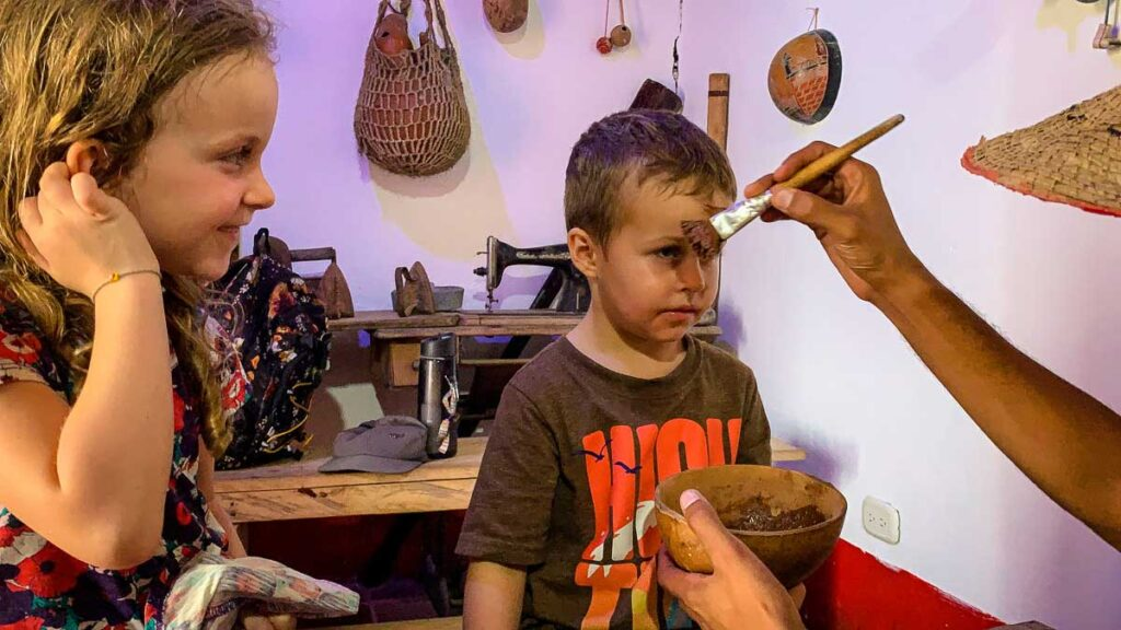a 4-year old gets his face painted with cacao paste at La Calendaria, Minca, Colombia
