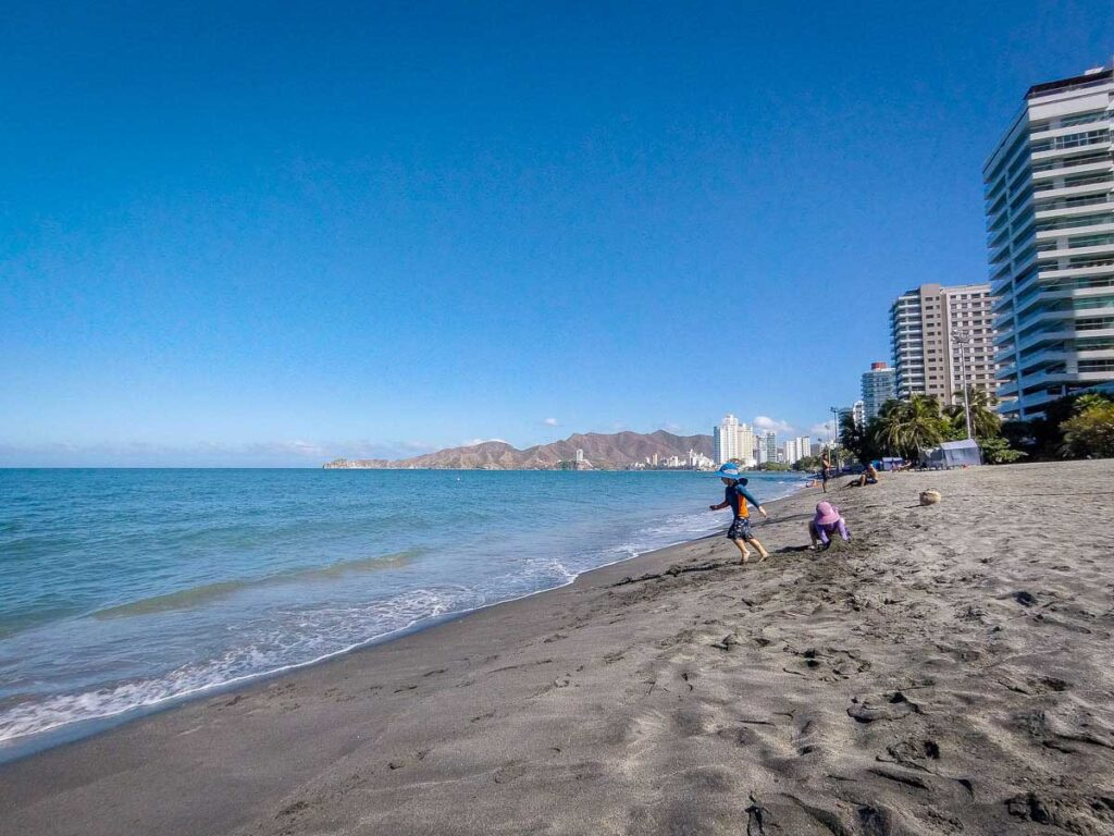 Kids play in the black sand on Salguero Beach in Rodadero, Colombia - a less busy alternative to Playa el Rodadero