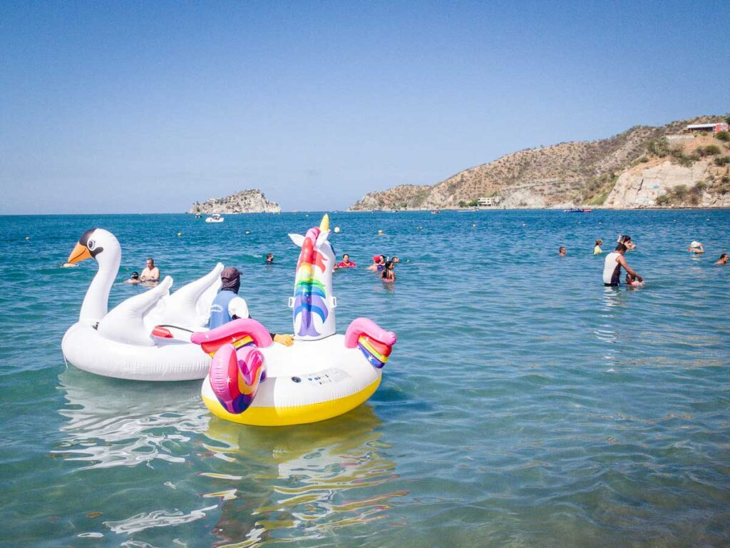 A vendor tries to rent an inflatable unicorn and a swan at Playa el Rodadero, Colombia
