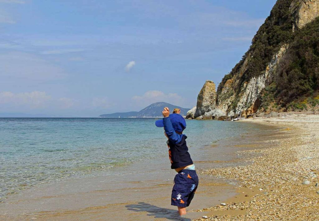 A toddler throwing rocks into the water at a Isola d'Elba beach