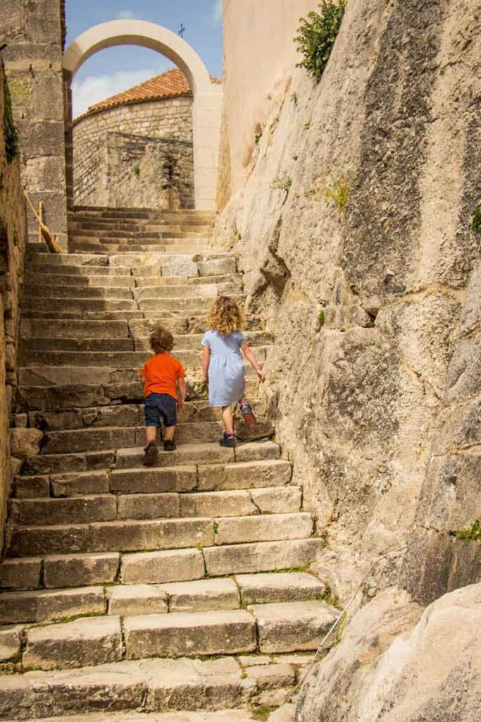 kids climbing stairs at Klis fortress - Fun things to do in Split for kids