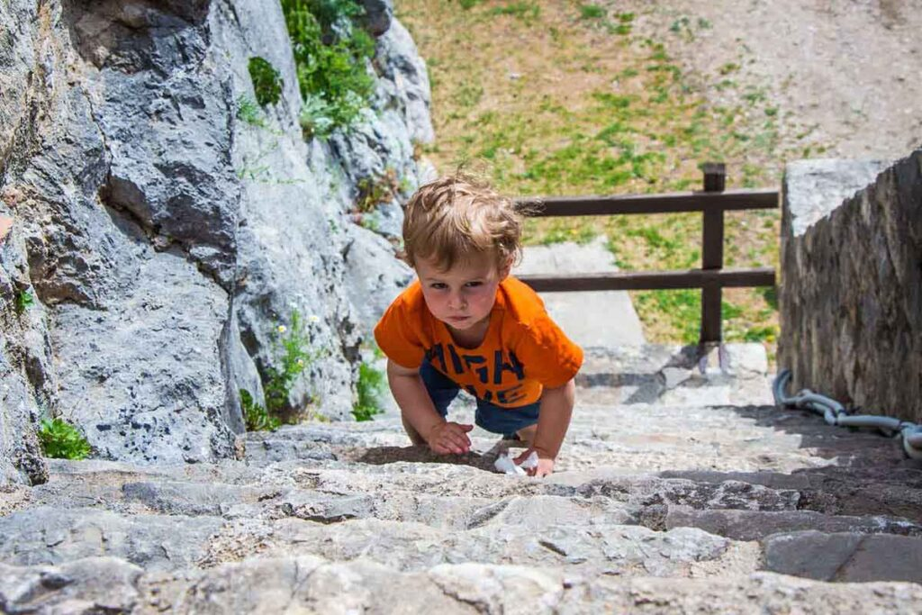 toddler climbing stairs at Klis Fortress in Split Croatia