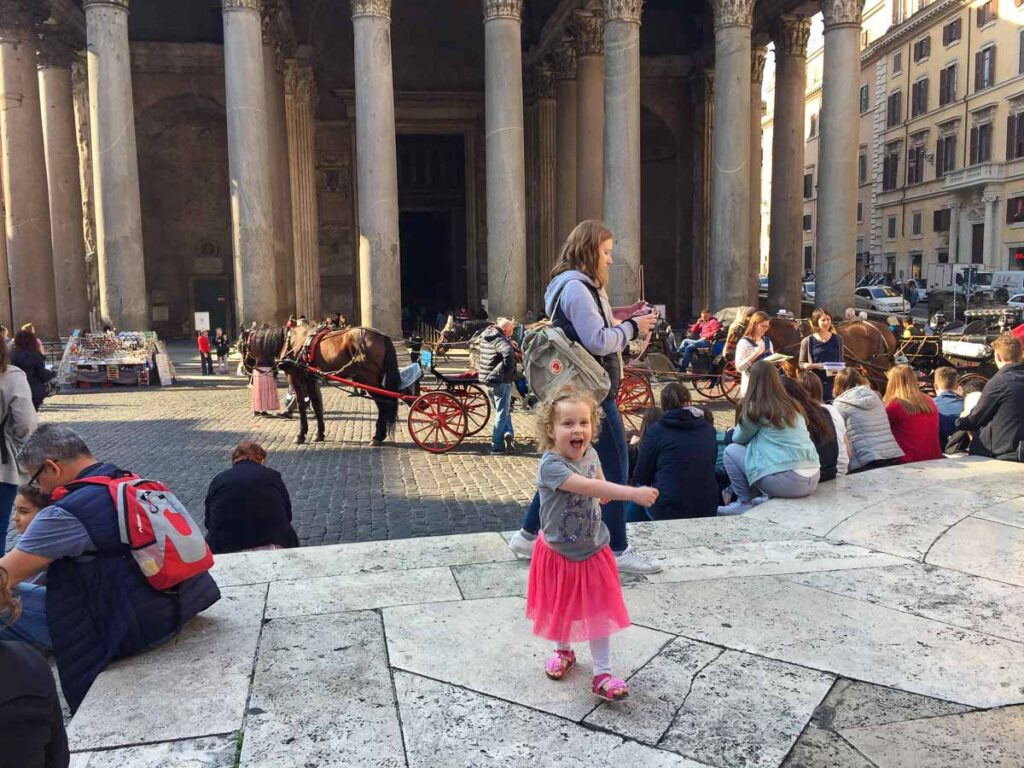 A happy child putting on a show in front of Rome's Pantheon building