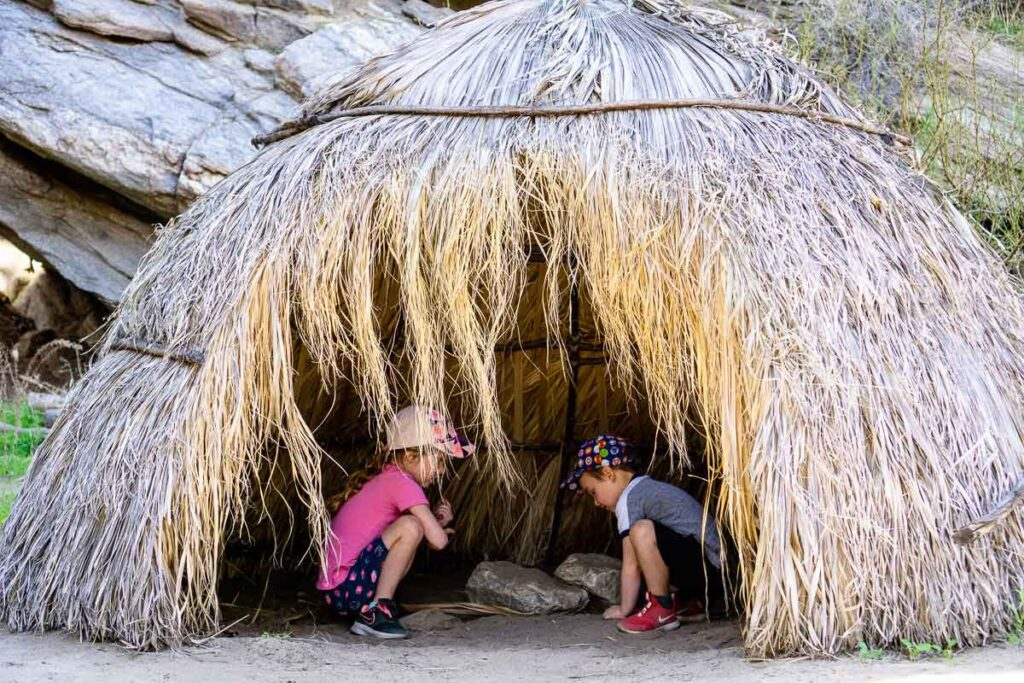 Small thatch huts to play in are one of the many reasons the Palm Canyon hike is a great thing to do with kids in Palm Springs