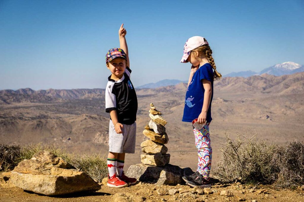 Two kids celebrate hiking to the summit of Ryan Mountain in Joshua Tree National Park
